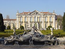 The front facade of the Queluz National Palace, with one of the ornate fountains