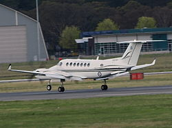 Colour photograph of a white aircraft flying just above an airport runway with its landing gear extended