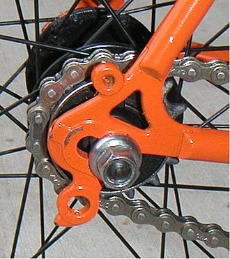 Fork end - A semi-horizontal dropout on a steel frame road bicycle converted to a single-speed. The non-replaceable derailleur hanger (below the axle) and an eyelet (above the axle) for mounting a fender or rack are now unused.