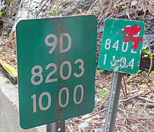 Two nearly adjacent markers, one slightly defaced with red ink, with slightly different sets of numbers