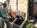 Removing treated faeces from UDDT in Nepal (4974455617).jpg