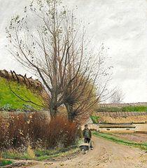 Autumn weather. A man with a wheelbarrow on a path