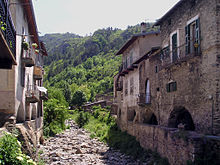 Photo of a dry, rocky streambed running straight through a town of old buildings