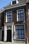 foto van Huis met verdieping, zadeldak en rijk gesneden deur met kalf in Lodewijk XV-trant, gevat in een omlijsting van verdiepte pilasters met hoofdgestel