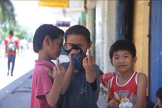 The finger - A group of homeless children from Keningauin, in Borneo, giving the finger while sniffing glue from a plastic bag.