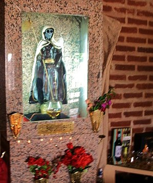San La Muerte - Statue of San La Muerte in central Argentina with alcohol offerings in the background.