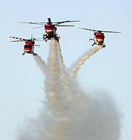 Drie helikopters vliegen in formatie, waardoor rook paden in de lucht