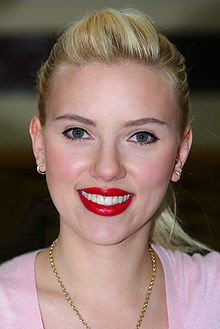The face of a smiling woman with blonde hair pulled back into a ponytail, wearing bright red lipstick, small gold hoop earrings, a heavy gold link chain around her neck, and a pink scoop necked shirt.