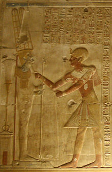 Relief showing an ornately dressed Egyptian man reaching toward a male figure on a pedestal.