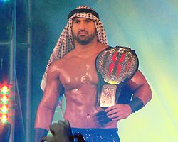 Daivari holding the TNA X Division Championship in front of a crowd.