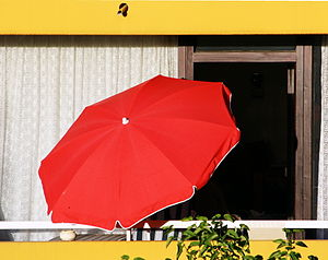 English: Red umbrella on a balcony. Sun protec...