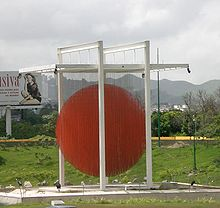 Daytime photo of sky, mountains, vegetation, a billboard, and, in the center of the image, poles with an orange circle in the center