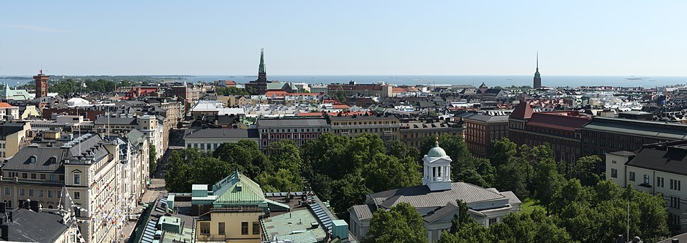 A panoramic view over the southernmost districts of Helsinki from Hotel Torni. The Helsinki Old Church and its surrounding park are seen in the foreground, while the towers of St. John's Church (near center) and Mikael Agricola Church (right) can be seen in the middle distance, backdropped by the Gulf of Finland.