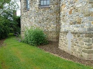 In de buitengevel achter het hoofdaltaar van de R.K. kerk, welke zelf niet op de lijst staat, bevinden zich stenen grafkruisen en fragmenten