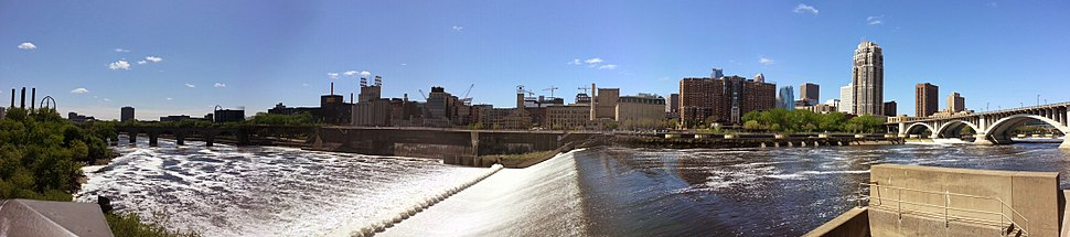 """Panoramic photo from the new Water Power Park, visible from this vantage: the lower portion of Saint Anthony Falls; the concrete wall on the far side of the falls is part of the locks to allow ships to pass the waterfall; to the left is the Stone Arch Bridge, above it is the Guthrie Theater; to the right of the Guthrie are the white silos and reconstructed shell of the former Washburn """"A"""" Mill, now the Mill City Museum; to the right of the museum are a series of redeveloped flour and grain mills making up a significant portion of the city's Mills District."""