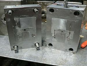 """Injection moulding - Standard two plates tooling – core and cavity are inserts in a mould base – """"family mould"""" of five different parts"""