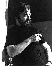 Greyscale image of Stephen Sondheim in a black t-shirt, looking to his left and holding a cigarette in his right hand.