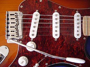 Electric guitar - Detail of a Squier-made Fender Stratocaster. Note the vibrato arm, the 3 single-coil pickups, the volume and tone knobs.