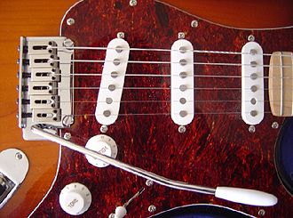 Detail of a Squier-made Fender Stratocaster. Note the vibrato arm, the 3 single-coil pickups, the volume and tone knobs. Stratocaster detail DSC06937.jpg