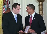 Stuart Milk speaks with Barack Obama, holding the case for the Presidential Medal of Freedom in the White House