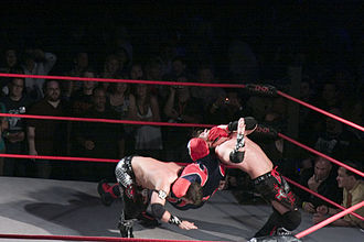 Suicide (wrestling) - Suicide performing a simultaneous neckbreaker/DDT combination on The Motor City Machine Guns.