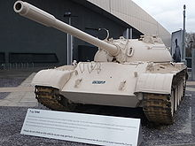 A tank, painted a light desert colour, facing the camera with a large metal-roofed building behind.