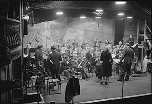 It's That Man Again - Charlie Shadwell (right) prepares to conduct the BBC Variety Orchestra during the recording of an episode of 'It's That Man Again' in 1945. On his left is Ann Rich, the 'ITMA' singer who succeeded Paula Green. To the left of the photograph, producer Francis Worsley chats to broadcaster Ronnie Waldman.