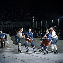 Five men playing hockey in a crowded arena.