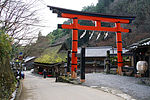 Large red torii next to a wooden thatched house.