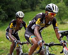 Two dark-skinned men riding bicycles.