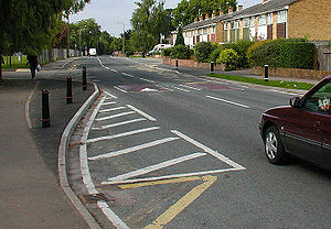 Curb extension - A curb extension marked by darkened tarmac and black posts.