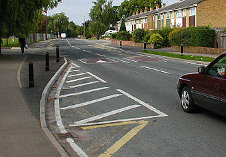 Curb extension - A curb extension marked by darkened tarmac and black posts