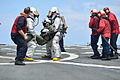 U.S. Navy Hull Maintenance Technician 1st Class Edward Buchanan, left, trains Hull Maintenance Technician Fireman Garrett Trotta and Damage Controlman 2nd Class Tavoris West during a flight deck crash 130807-N-YZ751-091.jpg