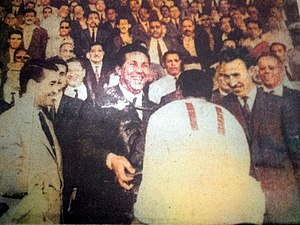 USM Alger - Ben Tifour, coach of the USM Alger receives from the hands of Ben Bella president, the first trophy Algerian football championship, under the gaze of President of the FAF the Dr Maouche (left) and Minister of Defense Houari Boumedienne (right).