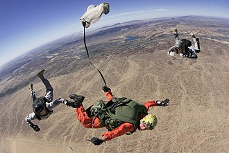 Military Freefall Parachutist Badge - Two MFFS instructors (in gray) assist a student as he freefalls over YPG