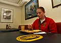 US Navy 030228-N-6077T-003 Sonar Technician 3rd Class Angila McCarty from Grandbury, Texas, enjoys dinner prior to assuming her temporarily assigned duties as a Food Service Attendant on the ship's mess decks.jpg