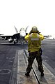 US Navy 030517-N-9319H-006 Aviation Boatswain's Mate 1st Class Patrick Reynolds, from Queen Creek, Ariz., directs an F-A-18E Super Hornet assigned to the Tophatters of Strike Fighter Squadron Fourteen (VFA-14) into positi.jpg
