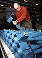 US Navy 040621-N-7748K-016 Aviation Ordnanceman 2nd Class Shawn Criswell, from Clarksville, Texas, stacks MK-76 practice bombs aboard the aircraft carrier USS Enterprise (CVN 65).jpg