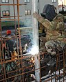 US Navy 050119-N-2306S-005 A Seabee, assigned to Naval Mobile Construction Battalion Four (NMCB-4), welds framework together.jpg