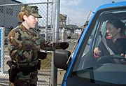 US Navy 050308-N-2385R-029 Master-at-Arms Seaman Carly Farmer checks an identification card (ID) before allowing a driver to enter the gate at U.S. Fleet Activities Sasebo, Japan