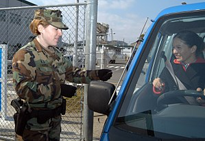 Authentication - A soldier checks a driver's identification card before allowing her to enter a military base.