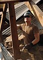 US Navy 051125-N-1261P-084 U.S. Navy Seabee Steelworker Benjamin Nablo, assigned to Naval Mobile Construction Battalion Seven Four (NMCB-74), dismantles a fallen structure at Mainbi Bundi Village.jpg