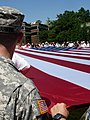 US Navy 062727-N-5362A-002 Local citizens and U.S. military personnel display a giant American flag during a.jpg