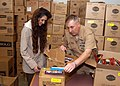 US Navy 070611-N-6247M-009 Command Master Chief (CMC) Francis Bagarella, CMC of Naval Air Station Whidbey Island, and Sherry Yates, Morale Welfare and Recreation Manager of Liberty and Operation Uplift Programs, open boxes of.jpg