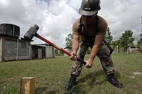 US Navy 070624-N-6278K-005 Utilitiesman 2nd Class Craig Gardener attached to Construction Battalion Maintenance Unit (CBMU) 202, hammers a board for a sidewalk at Belize Rural High School.jpg
