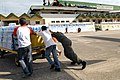 US Navy 080627-N-0640K-317 Aviation Structural Mechanic 2nd Class Myron Robertson, of Carson, Calif., helps local Philippine residents push a cart full of supplies at Kalibo Airport.jpg