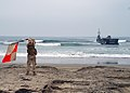 US Navy 080706-N-4973M-009 Seaman Nicholas Minadeo, assigned to Beach Master Unit (BMU) 1, waives the uniform flag to guide Improved Navy Lighterage System (INLS) Causeway Ferry 1.jpg