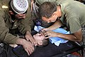 US Navy 090811-M-0440G-138 An Afghan boy gets treated for a head wound by Navy Corpsman Brian Sandou.jpg