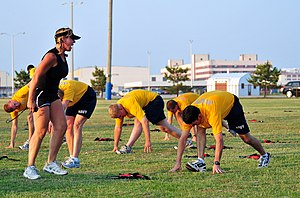 Fitness professional - U.S. Navy sailors exercising in the presence of a female fitness instructor, 2010.