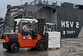 US Navy 100927-N-4971L-053 Hugh Grandstaff, third mate aboard High Speed Vessel Swift (HSV 2), moves a pallet of Project Handclasp Relief supplies.jpg